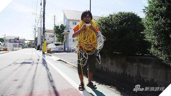 Thanh niên Nhật nối dây điện từ nhà ra ngoài đường để chơi game di động